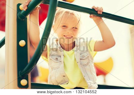 summer, childhood, leisure and people concept - happy little girl on children playground climbing frame
