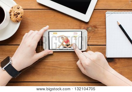 technology, sport and people concept - close up of woman with fitness application on smartphone screen and coffee cup on wooden table