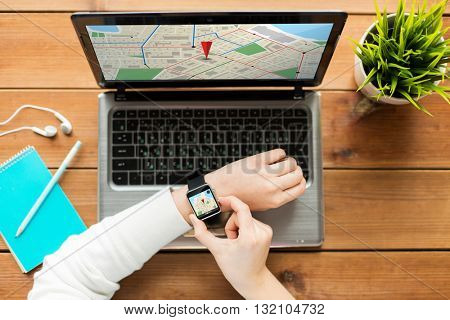 navigation, location, business, people and technology concept - close up of woman with smart watch and laptop computer on wooden table with gps navigator map on screens