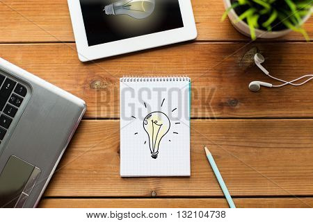 business, startup, idea and technology concept - close up of notebook with light bulb, laptop and tablet pc computer with