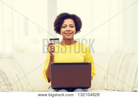 people, internet bank, online shopping, technology and e-money concept - happy african american young woman sitting on sofa with laptop computer and credit card at home