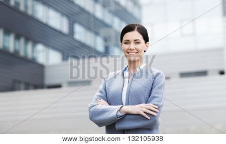 business and people concept - young smiling businesswoman over office building