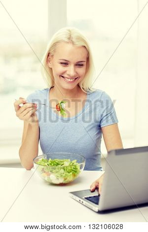 healthy eating, dieting, food, technology and people concept - smiling young woman with laptop computer eating vegetable salad at home