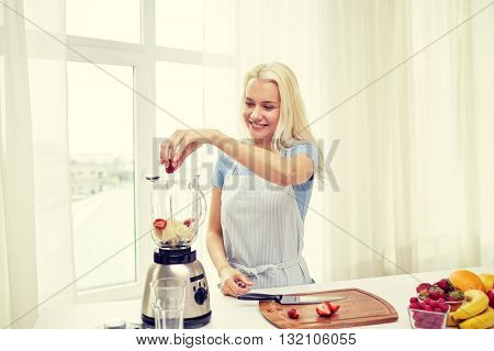 healthy eating, cooking, vegetarian food, dieting and people concept - smiling young woman putting fruits and berries for fruit shake to blender shaker at home