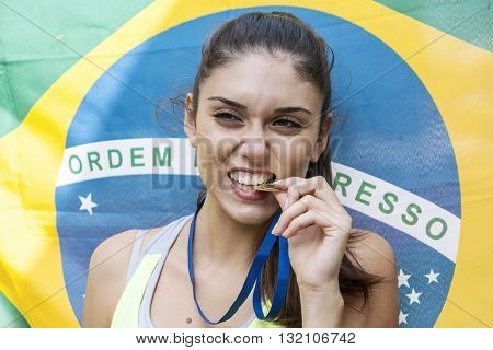 athlete shows the gold medal winner in fron of flag