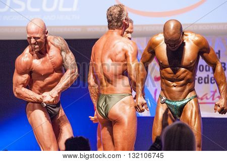 MAASTRICHT THE NETHERLANDS - OCTOBER 25 2015: Male bodybuilders flex their muscles and show their best physique on stage at the World Grandprix Bodybuilding and Fitness of the WBBF-WFF