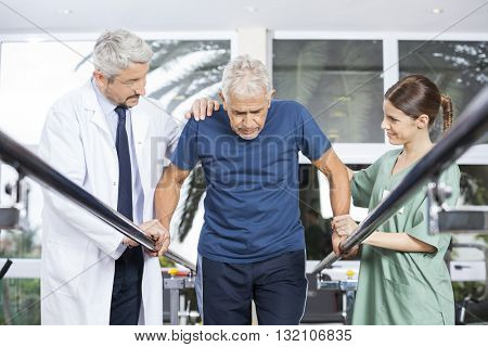 Physiotherapists Motivating Senior Patient To Walk Between Paral