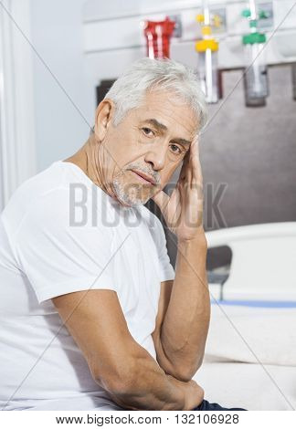 Sad Male Patient Sitting On Bed At Rehab Center