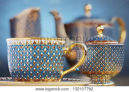 Thai fine art traditional five colors (Bencharong) tea cup over blue blurry background.