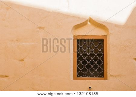 Orange well preserved wall with a window with an arch. Former capital of Malta - Mdina. Fusion of arabian architecture and baroque.