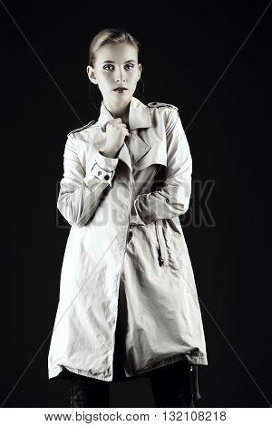 Fashion shot of a female model posing at studio in a coat. Beauty, fashion.