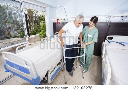 Caretaker Helping Senior Patient With Walker