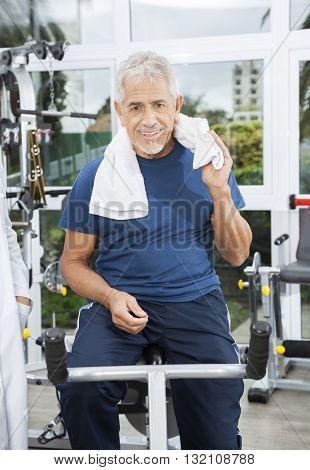 Senior Man Sitting On Exercise Bike At Rehab Fitness Center