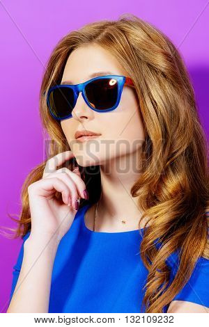 Bright summer style. Pretty young woman with beautiful hair slightly smiling at camera. Cosmetics, make-up. Hair care.