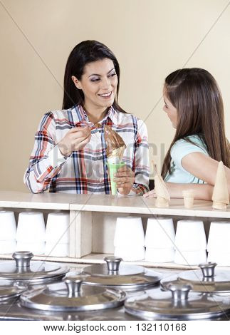 Woman Having Ice Cream With Daughter At Counter