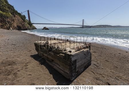 Broken piece of wooden dock washed up on beach with San Francisco and the Golden Gate bridge in background.