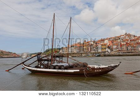 PORTO PORTUGAL - MAY 25 2016: Traditional Rabelo boats (used for port wine transportation) on Douro River in Porto Portugal. Historical part of Porto city (UNESCO site) at the background