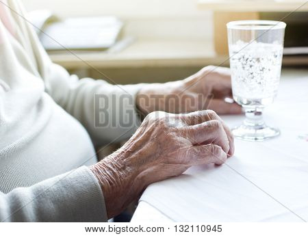 Close up of old woman's wrinkled hands on table with glass of water