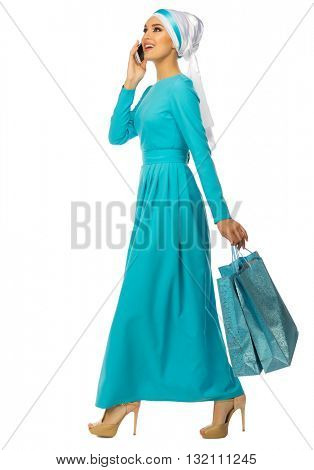Muslim woman with mobile phone and bags isolated