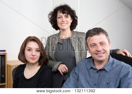 Three People At Work Smiling At The Camera