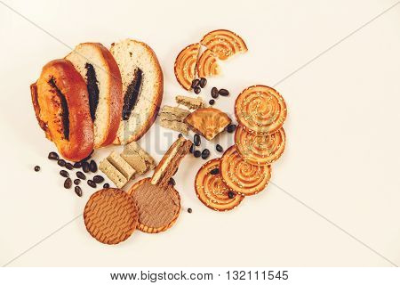 There are Pieces of  Roll with poppyseed,Cookies,Halavah,Chocolate Peas,Tasty Sweet Food on the White Background,Top View,Toned
