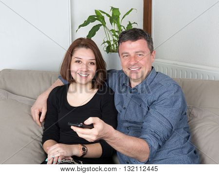 Smiling Couple Watching Tv On The Couch At Home