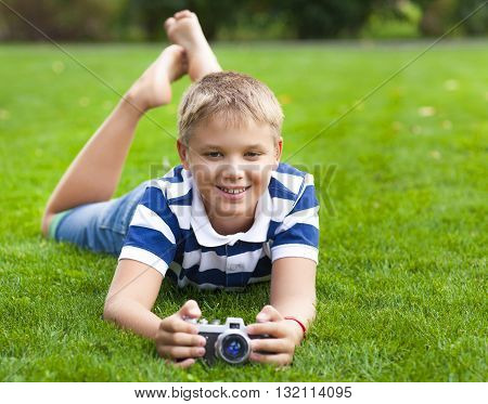 Happy smiling little boy with retro vintage camera in summer park
