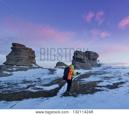 man with backpack and poles going in mountains and rocks snow covered at purple sunset