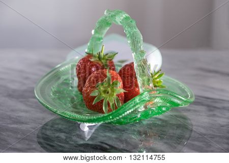 Strawberries In Green Glass Dish On Napkin And Marble