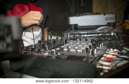 Mixing Console and the hand of the DJ in a nightclub