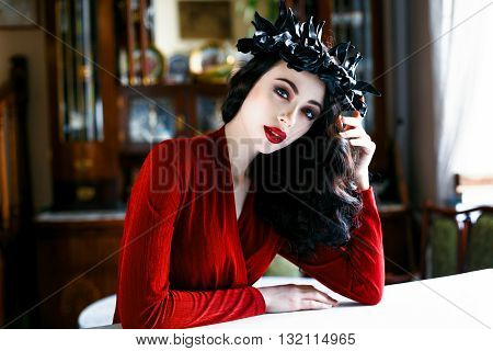 Beautiful model with a rad and black wreath of flowers on her head