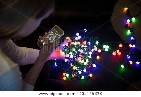 Hand girl photographed on a mobile phone colorful garlands of lights