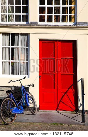Red door and blue bicycle on entrance in old european house, Amsterdam.
