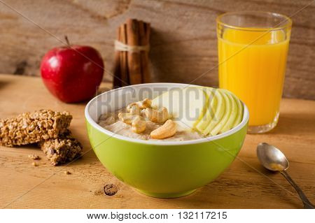 Oatmeal porridge with apples, cinnamon, nuts and goji berries. Granola bars, fresh fruits and glass of orange juice on background. Healthy breakfast concept. Close up