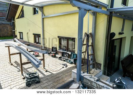 Building a canopies on a residential house. Building a metal construction for residence shading.