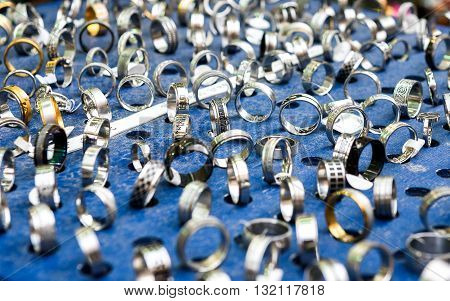 Display With Different Designs Of Handmade Silver Rings On Blue Stand