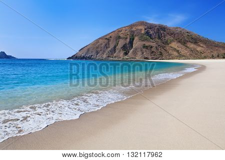 Beautiful scene on best desert beach with white sand clear water on ocean bay Mawun in tropical island Lombok. Boundless tropic beach with no people in lost paradise. Travel and vacation in Indonesia