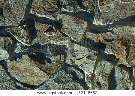 Stone wall grey uneven cracked surface on rock background