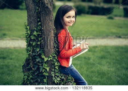 Girl With Notebook And Pen Near Tree