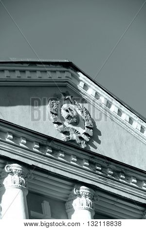 Emblem of USSR on the building. Part of the roof. Monochrome image