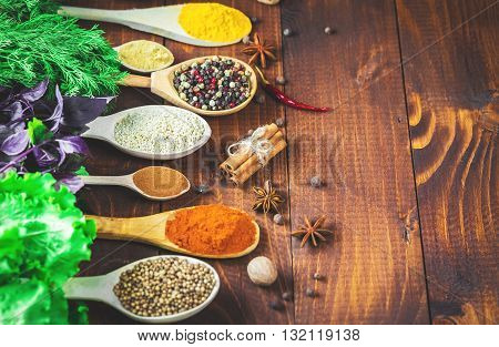 Beautiful Colorful Spices In Wooden Spoons And Bowls With Lettuce, Dill And Basil On An Old Wooden B
