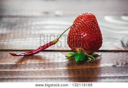 Hot Red Chili Pepper With Strawberries On Old Wooden Background. The Concept Of Novelty And Unexpect