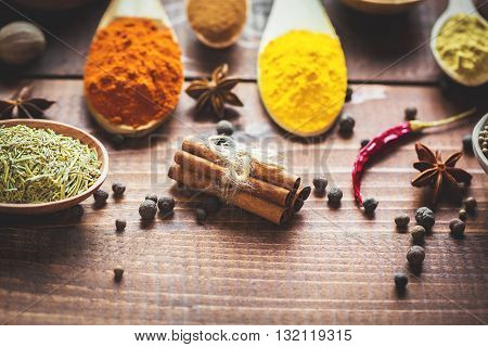 Beautiful Colorful Spices In Wooden Spoons And Bowls On An Old Wooden Brown Table.