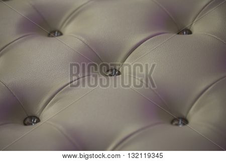 Buttoned white leather wall with vignetting on padding background