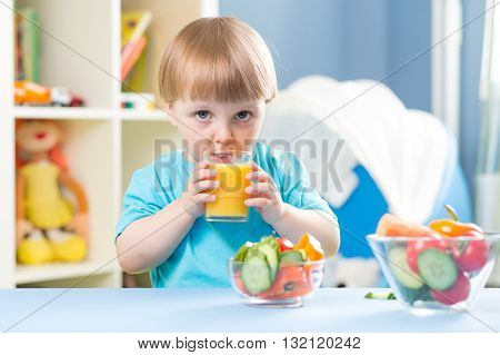 child boy drinking juice from glass and eating vegetables indoors