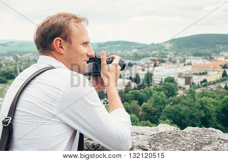 Man with professional photo camera take landscape picture