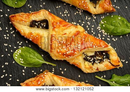 Puff pastries with spinach, cheese  and sesame seeds on black background.