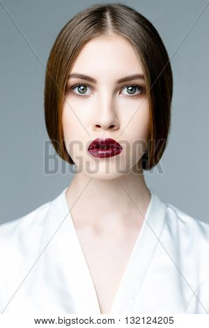 Beauty fashion girl. Portrait of beautiful young woman with fresh clean skin on grey background