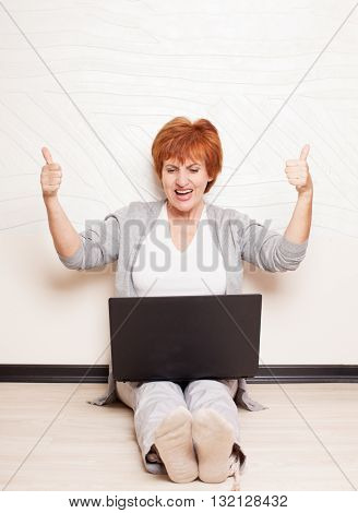 Woman sitting on floor with laptop. Mature female at home. successful