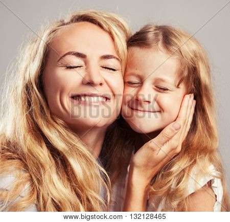 Mother with little girl. Parent with child. Happy family clouse up squint